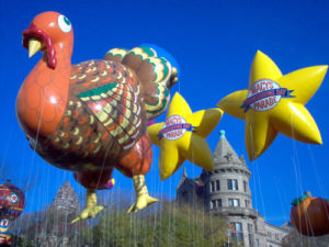giant 20ft tall turkey helium parade balloon in air with two yellow star balloons